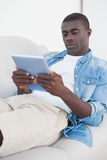 Casual man lying on sofa using his tablet pc Royalty Free Stock Photo