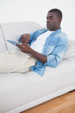 Casual man lying on sofa using his tablet pc Royalty Free Stock Photos