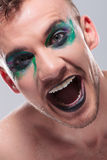 Casual man with makeup laughs out loud. Closeup of a casual young man with dramatic makeup laughing out loud with mouth opened. on gray background royalty free stock photo