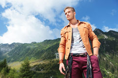 Casual man in mountains holds a hand in pocket and looks away Stock Images