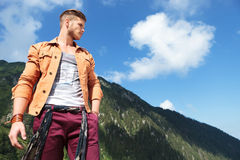 Casual man from mountains looks away with hand in pocket Stock Image
