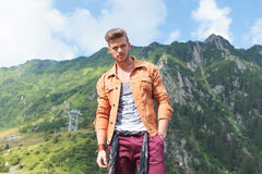 Casual man in mountains looks at you with hand in pocket. Young casual man standing outdoor with a hand in his pocket and looking into the camera Royalty Free Stock Photo