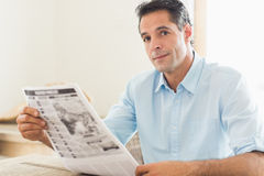 Casual man with newspaper looking away in kitchen Royalty Free Stock Images
