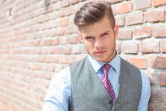 Casual man next to a brick wall Stock Images
