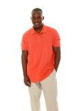 Casual Man In Orange Shirt. Casual young African American man standing in an orange golf shirt Royalty Free Stock Images