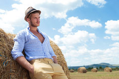 Casual man outdoor with both hands in pockets. Young casual man posing outdoor with both hands in pockets and looking away while leaning back on a haystack Royalty Free Stock Photos