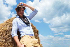 Casual man outdoor on haystack looking at you Royalty Free Stock Photos