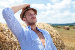 Casual man outdoor leaning back on haystack Stock Images