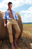 Casual man outdoor leans on haystack and looks away Stock Images
