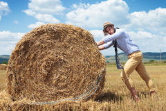 Casual man outdoor looks at you and pushes haystack Royalty Free Stock Photography