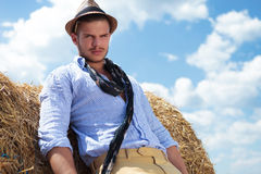 Casual man outdoor next to haystack, looks at you Royalty Free Stock Image