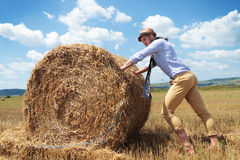 Casual man outdoor pushes a haystack Royalty Free Stock Photography