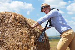 Casual man outdoor pushing a big round haystack Stock Images