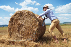 Casual man outdoor pushing a haystack Stock Photography