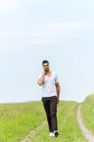 Casual man walking outdoors Stock Images