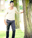 Casual man outdoors leaning on a tree Royalty Free Stock Photography