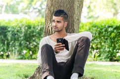 Casual man using phone outdoors Stock Photos