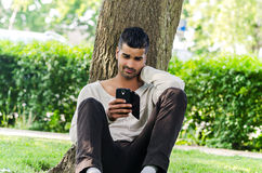 Casual man using phone outdoors Stock Image