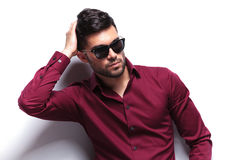 Casual man passes hand through hair. Young casual man passing his hand through his hair while looking away from the camera. on white background Royalty Free Stock Image