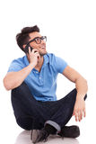 Casual man on the phone, looks up. Appealing young casual man speaking over the phone and sitting with his legs crossed. He is looking somewhere up and smiling Royalty Free Stock Photos