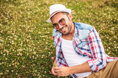 Casual man picking a flower from a field and smiles Royalty Free Stock Images