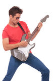 Casual man plays guitar. Casual young man passionately playing on an electric guitar. isolated on a white background Royalty Free Stock Images