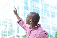 Casual man pointing with his finger to the building stock images