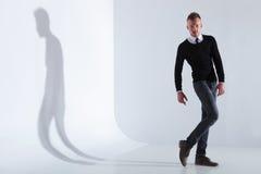 Casual man poses with a bent leg Stock Photos