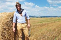 Casual man posing next to haystack Royalty Free Stock Photos
