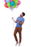 Casual man presenting a bunch of baloons Royalty Free Stock Image