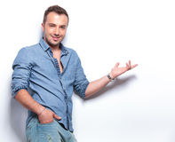 Casual man presenting with hand in pocket Royalty Free Stock Images