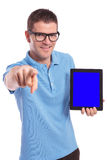 Casual man presents tablet and points at you Royalty Free Stock Photos