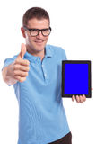 Casual man presents a tablet and shows the thumb up gesture Royalty Free Stock Photo