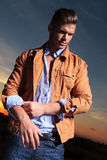 Casual man pulls up his sleeve at sunset Stock Images