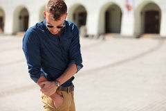 Casual man reaching into pocket. Casual young man reaching into his pocket and looking at it in the city royalty free stock images