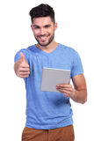 Casual man reading good news on his tablet pad Royalty Free Stock Photography