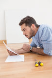 Casual man reading instruction manual for power tool Royalty Free Stock Photos