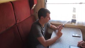 Casual man reading lifestyle from mobile phone screen while reads sms message traveling on train wagon. slow motion. Video. Wireless social media internet web stock video