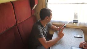Casual man reading from mobile lifestyle phone screen while reads sms message traveling on train wagon. slow motion. Video. Wireless social media internet web stock video