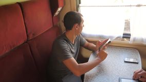 Casual man reading from mobile phone lifestyle screen while reads sms message traveling on train wagon. slow motion. Video. Wireless social media internet web stock video footage