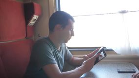 Casual man reading from mobile phone screen while reads sms message traveling on train wagon. slow motion video. Wireless social media internet web on public stock video