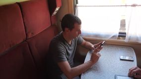 Casual man reading from mobile phone screen while reads sms message traveling on train wagon. slow motion video. Wireless social media internet web on stock video