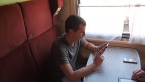 Casual man reading from mobile phone screen while reads sms message traveling on train wagon. slow motion video. Lifestyle . Wireless social media internet web stock video footage