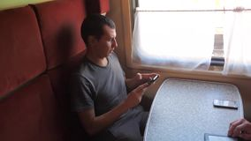 Casual man reading from mobile phone screen while reads sms message traveling on train wagon. slow motion video. Wireless lifestyle social media internet web stock video
