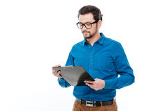 Casual man reading something in clipboard Stock Photography
