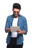 Casual man reading something on a computer tablet. Royalty Free Stock Image