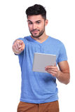 Casual man reading on a tablet pad is pointing Royalty Free Stock Images