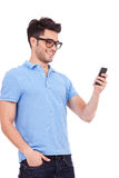 Casual man reading a text on his phone. Young casual man reading something on his phone and smiling Royalty Free Stock Photo