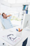 Casual man resting with hands behind head in office Stock Image
