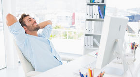 Casual man resting with hands behind head in office Royalty Free Stock Images